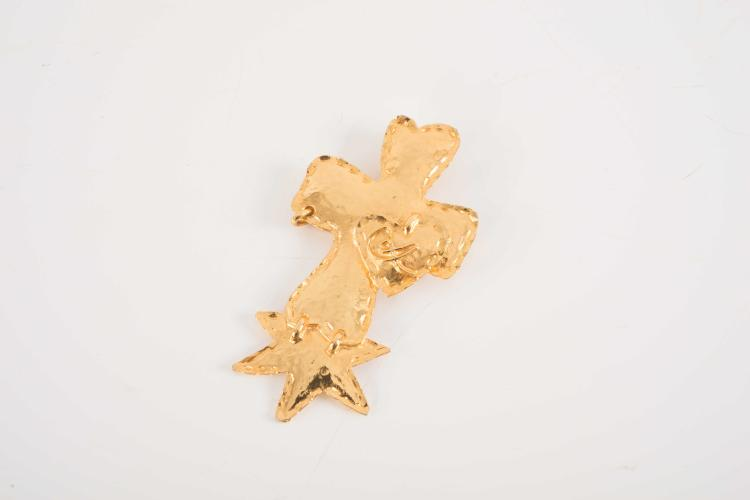 CHRISTIAN LACROIXBroche en métal doré représentant une croix.Bon état. Dans son pochon