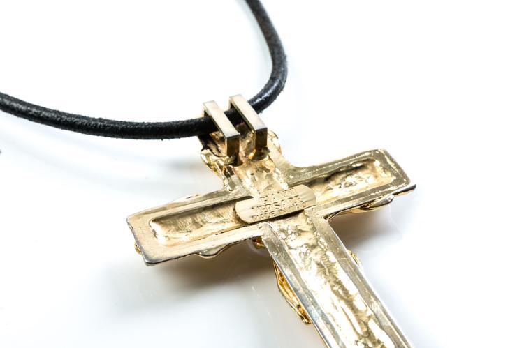 VERSACE  Pendentif croix en métal doré retenu par un cordon noir.