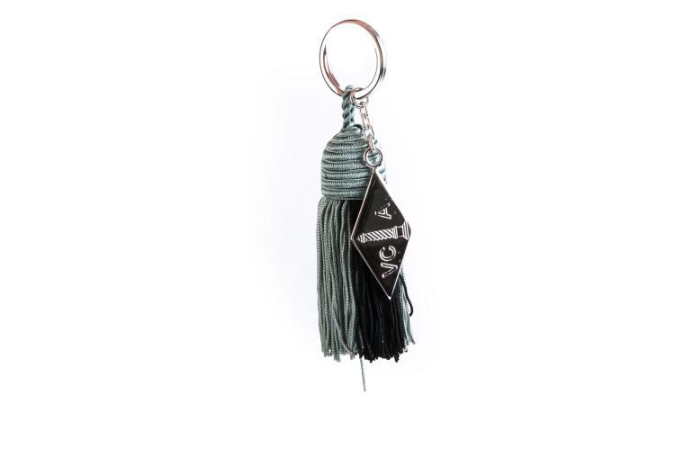 VAN CLEEF & ARPELS Porte-clé en métal argenté retenant un pompon vert et noir.