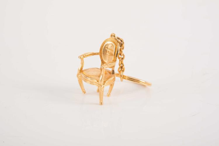 CHRISTIAN DIOR  Porte-clé en métal doré en forme de fauteuil.