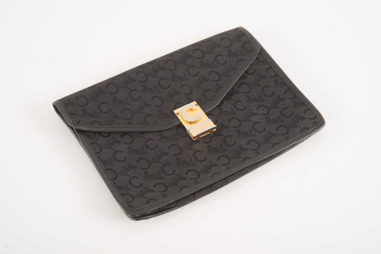 CELINE PARIS Made in FrancePochette souple en tissu monogrammé noir bordée de cuir noir. Fermeture par une jolie attache en métal doré ornée d'un