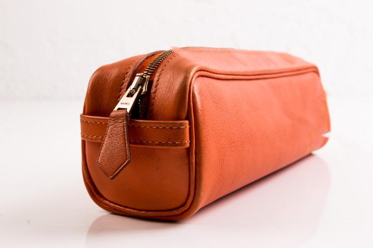 HERMES Trousse en cuir orange zippée.