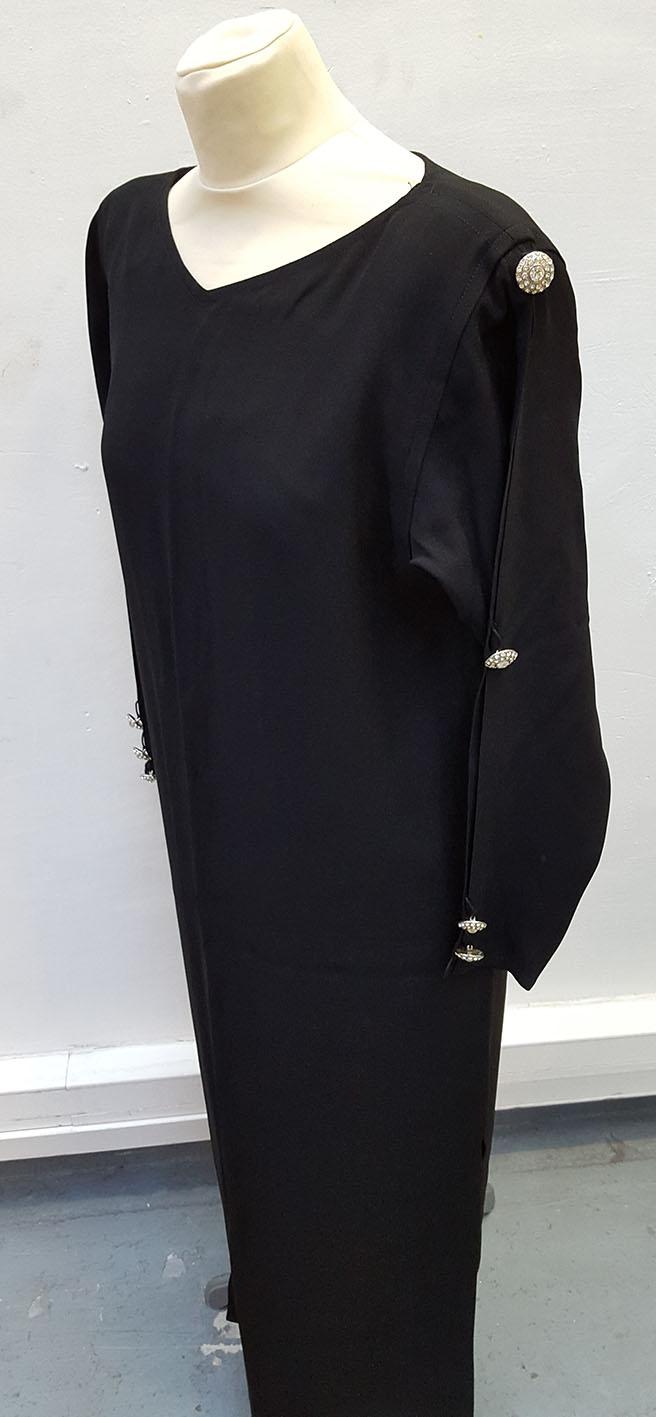 YVES SAINT LAURENT Rive Gauche  Robe longue noir, manches longues ajourées retenues par des boutons sphériques strassés et trois boutons au tour de poignet.