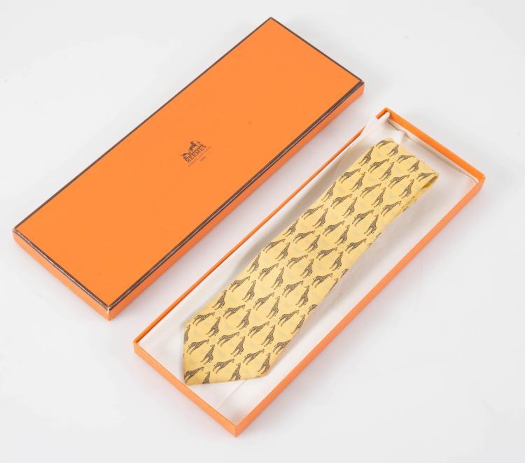 HERMES PARIS Cravate en soie jaune imprimée de girafes.