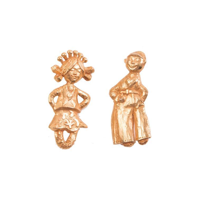 CHRISTIAN LACROIX - Made in France  Deux broches en métal doré représentant un petit garçon et une petite fille.