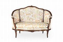 Mobilier de salon de style Louis XV en noyer    mouluré et sculpté de fleurs comprenant : un petit    canapé corbeille et une paire de bergères à dossier    cintré et garni avec accotoirs à manchettes; pieds    cambrés. Recouvrage de tissu imprimé.