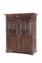 Petite armoire Louis XIII en noyer à montants plats sculptés de graines et de feuillages. Elle ouvre à 2 portes à plates-bandes rectangulaires et sculptées de rinceaux de fleurs. Linteau centré d'une tête d'angelot entre des feuilles d'acanthe et