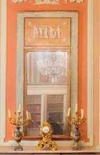 Glace-trumeau sur fond de parclose laquee gris-vert avec encadrement en bois dore a frise d ' oves et fil perle. En partie haute 5 personnages a l ' Antique en stuc dore.