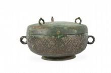 Recipient à aliments couvert en bronze, Dou Chine, Fin des Royaumes Combattants - début de la Dynastie Han, IIIème siècle av. J-C. En forme de sphère aplatie reposant sur un petit pied évasé, le pourtour décoré de motifs archaïques, deux petites