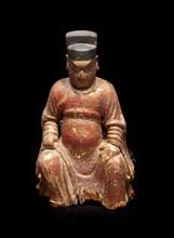 Dignitaire en bois laqué rouge et or Chine, XVIIème siècle. Représenté assis vêtu d'une longue robe et coiffé d'un bonnet de dignitaire. La main gauche appuyée sur les genoux, la droite retenant un pli de la robe. Manques dus aux xylophages à la