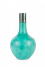 Vase en porcelaine à glaçure vert-turquoise Chine, XVIIIème siècle. La panse de forme ovoïde, surmontée d'un long col tubulaire, incisée d'un décor de chimères ; col réduit et remplacé par une bordure de métal, petits éclats sur la panse. H. : 44 cm.