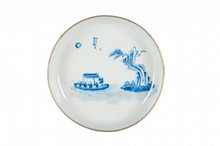 Coupelle en porcelaine bleu blanc  Vietnam, XIXème siècle.  A décor de barque, personnages, rocher et arbre, une inscription au  dessus de la scène, la bordure cerclée de métal, marque à la base.  D. : 14,5 cm.