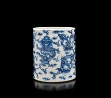 Pot à pinceaux en porcelaine bleu  blanc  Chine, XXème siècle.  A décor de dragons évoluant au milieu des  nuages, marque apocryphe à la base. H. : 12 cm.