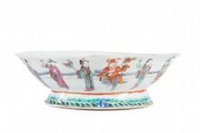 Coupe en porcelaine polychrome  Chine, fin du XIXème siècle.  De forme ovale, la bordure lobée, reposant sur  un pied, décorée de personnages alignés sur une  terrasse, la base ornée d'une frise de vaguelettes.  L. : 19 cm. ; H. : 8 cm.