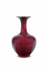 Vase en porcelaine à glaçure sang de boeuf  Chine, XIXème siècle.  De forme balustre, la panse terminée par un long col évasé ; éclat au col, coups à la base. H. : 35 cm.
