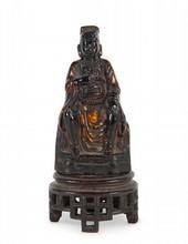 Statuette de Dignitaire en bronze laqué rouge et or Chine, XVIIème siècle. Représenté assis, la main gauche posée sur son genou et la droite sur le plastron, vêtu d'un manteau aux plis tombants, coiffé du bonnet de dignitaire, socle en bois. H. : 12