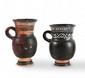 DEUX OLPÉS  En céramique lustrée noir, décorés de motifs géométriques  peints.  Grande Grèce. Epoque hellénistique.  H. : 13 et 11 cm.