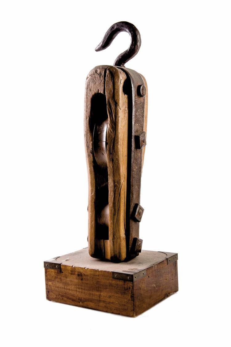 Poulie double réa présentée sur un socle, début XXe. 66 cm.
