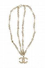 CHANEL - Sautoir en perles blanches et métal doré, orné d'un pendentif figurant le sigle de la marque.   Circa 2010.     Très bon état.