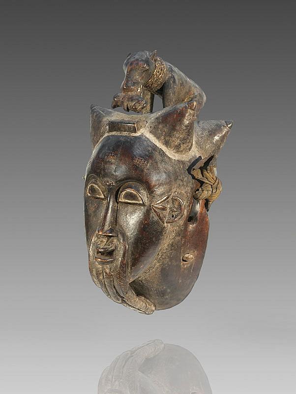 Important masque du Goli BAOULÉ, Côte d'Ivoire. Visage expressif, coiffe à quatre cornes, longue barbe composée de tresses recourbées vers le cou. Rare représentation au sommet d'une panthère évoquant la dignité Amwin, tenant dans sa gueule le chien