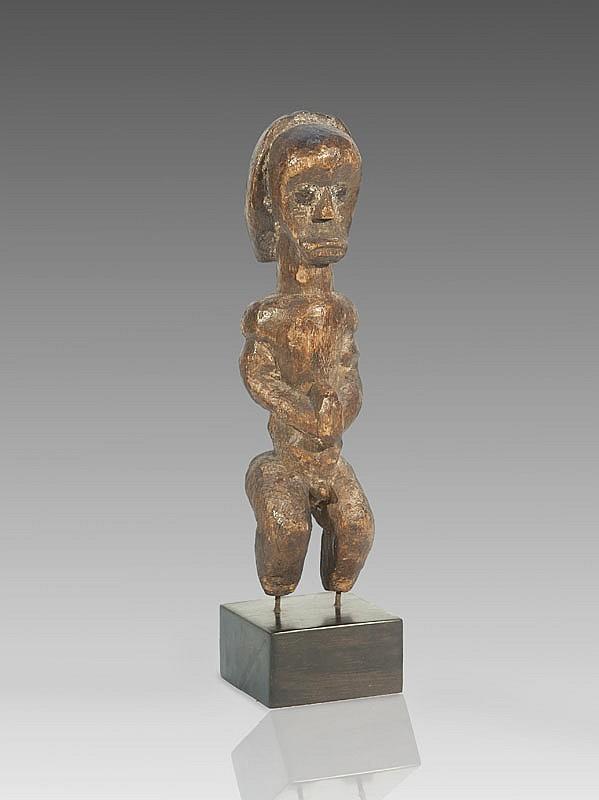 Petit reliquaire    FANG, style Ntumu, Gabon.  Statuette dite Byeri aux volumes équilibrés.  Bois à patine brun clair. Pieds manquants.  H. : 30 cm.