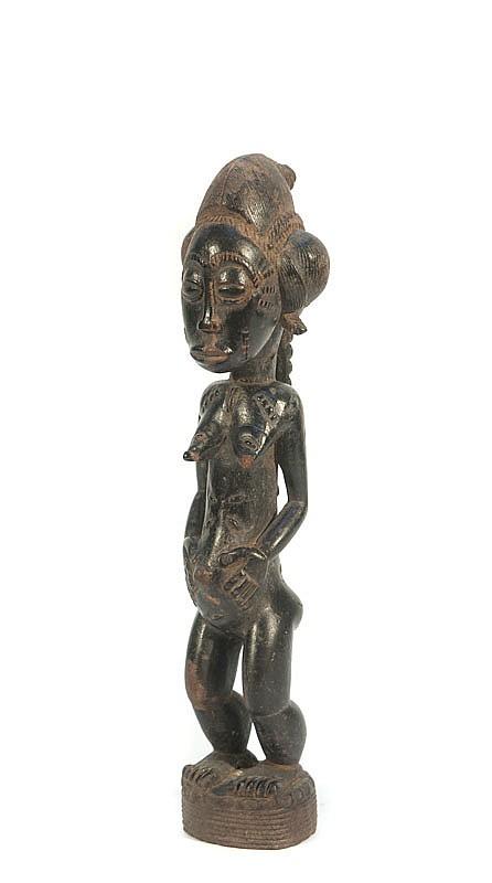 Statuette Blolo Bla  BAOULÉ, Côte d'Ivoire.  Représentation de l'épouse céleste. Coiffure en coque et tresses  ouvragées.  Bois à patine brun noir.  H. : 29,5 cm.