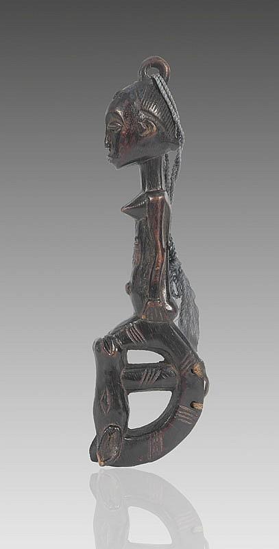 Marteau de gong BAOULÉ, Côte d'Ivoire. Manche surmonté d'une statuette représentant une femme sculptée dans une pose hiératique: debout, le corps droit, la tête dans son prolongement. Le percuteur figurant une tête de bovidé traitée de façon