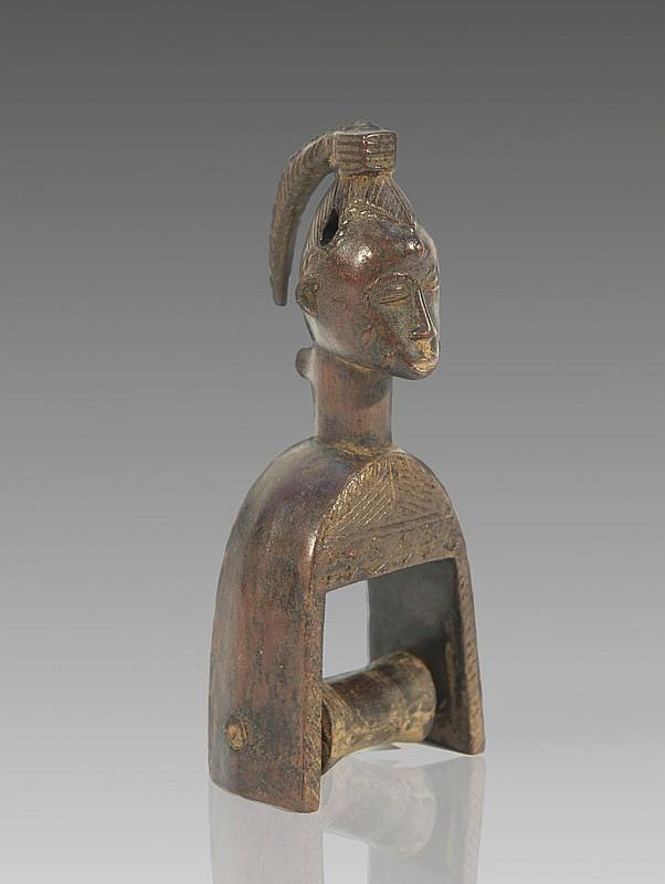 Etrier de poulie de métier à tisser GOURO, Côte d'Ivoire. Superbe visage à la longue coiffe en natte tressée projetée vers l'arrière. Bois à patine brune. H.: 16,5 cm.