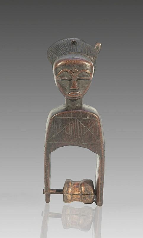 Etrier de poulie de métier à tisser BAOULÉ, Côte d'Ivoire. Surmontée d'un beau visage à la coiffe traité en crête tendue vers l'arrière. Bois à patine brun roux. H.: 18 cm.