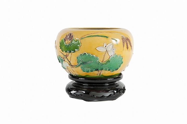 Petite vasque en porcelaine émaillé, jaune, vert et aubergine et son socle Chine, fin du XIXe siècle. De forme bombée à décor à relief d'échassiers et fleurs de lotus sur fond jaune. Le socle en céramique émaillée brun foncé. Marque à la base. D. :