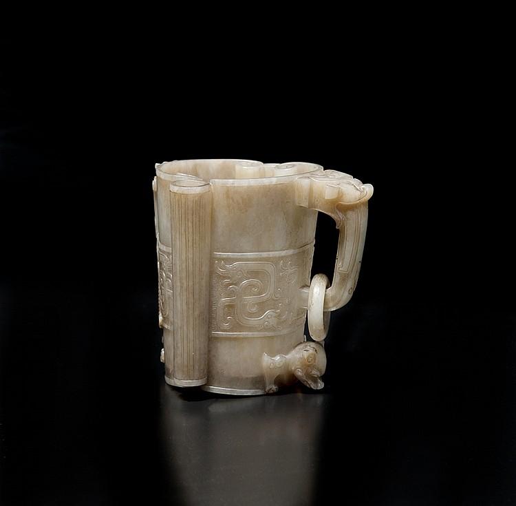 Vase en jade « gras de mouton » et brun Chine. En forme de deux rouleaux aux extrémités enroulées, accolés et maintenus ensemble par deux cylindres cannelés, une anse surmontée d'un masque de taotie et supportant un anneau mobile sur une des faces,