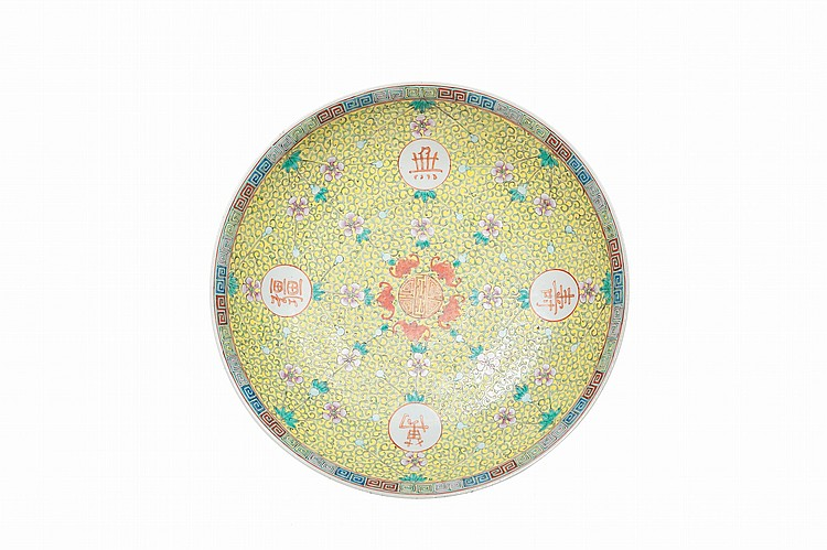 Grand plat en porcelaine polychrome Chine, début du XXème siècle. Décoré au centre d'un caractère shou entouré de cinq chauve-souris et de quatre médaillons contenant les caractères wan shou wu jiang, voeux de longévité, sur fond jaune de rinceaux et