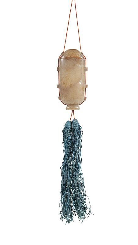 Petit vase suspendu couvert en jade  Chine, XIXème siècle.  La surface polie, de couleur gris-rouille. Les côtés  agrémentés de passants pour le cordon. Petit accident  au couvercle et manque à son extrémité.  H. : 6,7 cm.