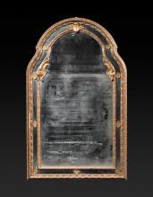 Miroir en bois doré de forme mouvementée, à double encadrement  à décor de feuillages et rosaces.