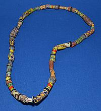 AFRICAN TRADE BEAD NECKLACE  African millefiore glass trade bead necklace.  60 total beads. Sizes 1/4 - 1 1/2''L.  Necklace 28''L.  Condition all jewelry sold as is.