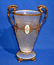 CZECH OPALESCENT GLASS VASE WITH METAL MOUNT Czech molded glass vase. Raised blossoming trees on body. Paneled opalescent glass base. Set in gilt metal cage with four feet. Two scrolling handler. Front oval enameled medallion. 12 1/4'' hieght. 6