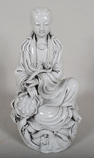 CHINESE BLANC DE CHINE QUANYIN. Blanc de chine porcelain figure of Quanyin seated on lotus base holding ruyi scepter (slight grey cast to porcelain). Marked: 2 impressed seal marks on back. Size: 11''H, 6''W, 5''deep. Condition: age appropriate wear.