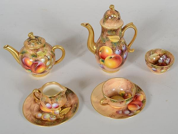 ROYAL WORCESTER MINIATURE TEA SET 7 PIECES. Royal Worcester porcelain miniature tea set, all with hand painted artist signed fruit decoration. Marked: Royal Worcester Fine Bone China England. Lot includes: (1) teapot, 3 1/2''H. (1) coffee pot 5''H.