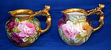 PAIR GINDRI PITCHERS Pair Gindri Italian Porcelain Pitchers. One with Hand Painted Roses on Gold Ground. One with Hand Painted Roses on Shaded Purple and Blue Ground. Gilt winged female figure. Handles, gilt rim. 7''H. 8''W. 6''diam.widest part.