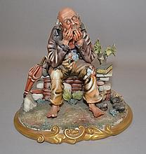 CAPODIMONTE FIGURE OF OLD MAN ON STONE WALL  Polychrome porcelain figure of an old man resting on a stone wall. Artist signed ''fiori''. 8 3/4''H.  Mark, fiori crown over N.  Condition, age appropriate wear.