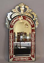 VENETIAN GLASS MIRROR  Clear and ruby glass venetian mirror. Arched top with decorative top finial. 30''H. 17 1/4''W.  No Mark. Condition, age appropriate wear. (some loss to silvering).