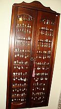 Large glazed cabinet with collection of souvenir