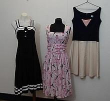 Three retro style dresses one pink example with a