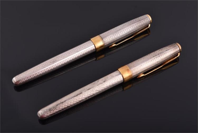 A pair of Parker engine turned silver pens including a fountain pen and a ballpoint, the fountain