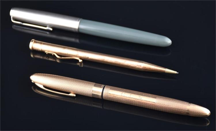 A 9ct gold Sheaffer fountain pen with 14K gold nib and engine turned body, and a 9ct gold propelling