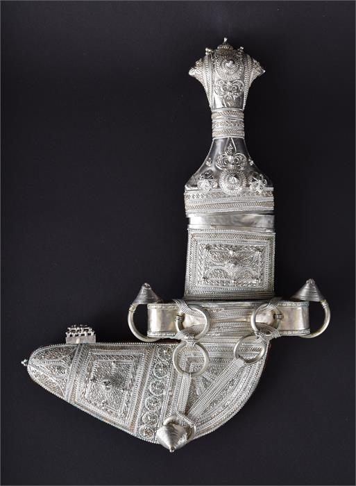 An intricately decorated Eastern white metal jambayah in a white metal scabbard and green