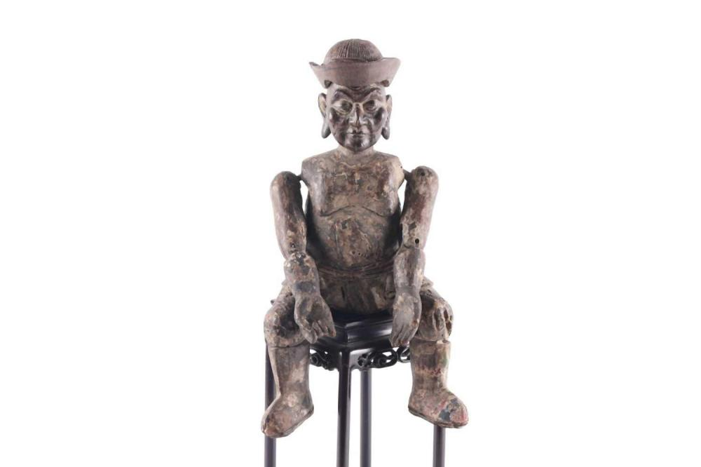 A Chinese carved wood articulated doll, Qing, modelled seated wea