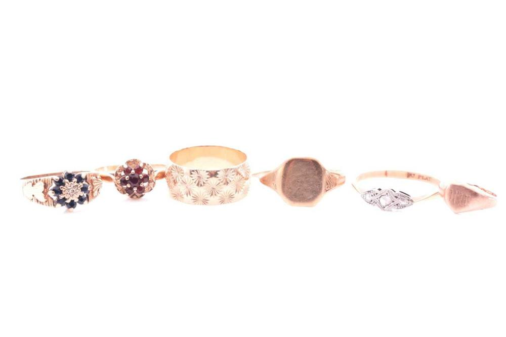 A group of six gold rings, to include a yellow metal and platinum ring with paste stones (mark indistinct due to resizing, likely 18ct), size T 1/2, together with a 9ct yellow gold and garnet ring, a 9ct gold and sapphire ring, a 9ct yellow gold...