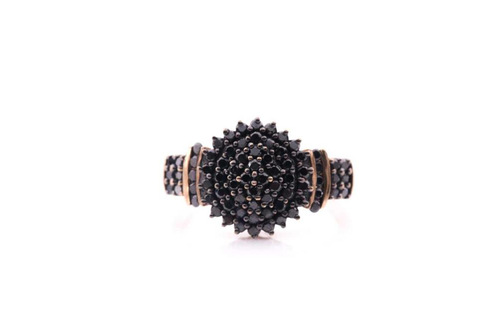A black diamond cluster ring; the bombé style circular centre set with multiple circular cut daimonds and with diamond set shoulders to a 9 carat gold shank. Total diamond weight estimated to be 1 carat; size S; 4.3 grams.