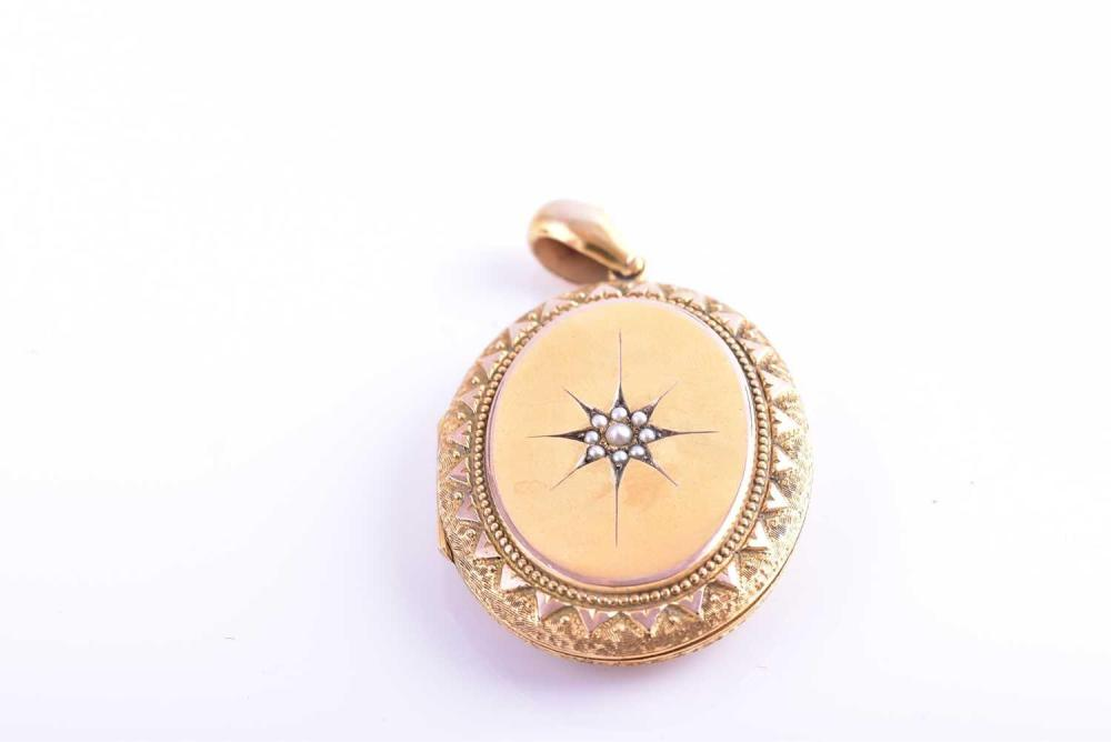 A Victorian yellow metal locket pendant, the hinged lid with starburst design inset with split seed pearls, the reverse with engraved floral design, opening to reveal double glass aperture, unmarked (tests as 15ct gold), locket 4 x 3.2 cm, 18.2...